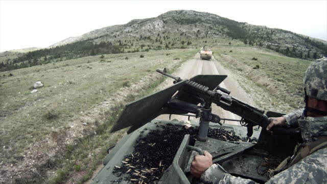 Soldier checks machine gun on humvee