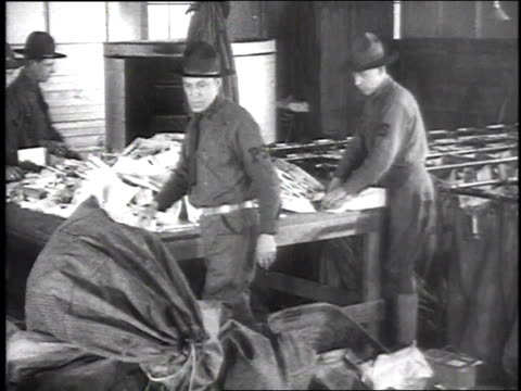 stockvideo's en b-roll-footage met ms soldier clerks in a mail room sorting letters standing on a table to dump out a full mailbag / camp sherman chillicothe ohio united states - chillicothe
