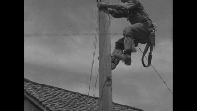 vídeos de stock e filmes b-roll de soldier climbs up utility pole next to houses along roadside, mountains in bkgd and jeep driving down road / us soldier climbs pole with wire draped... - cilindro veículo terrestre comercial