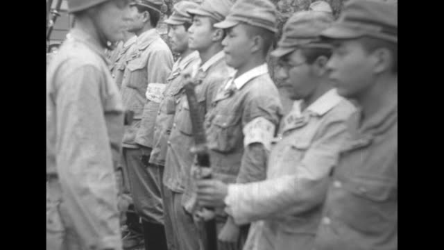 a us soldier collects swords from japanese men and hands them off to another with an armful of the weapons / scores of japanese soldiers march away... - japanese surrender stock videos and b-roll footage