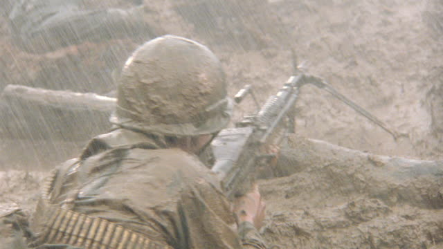 a soldier crawling in a raining mud field gets shot in battle. - vietnam war stock videos & royalty-free footage