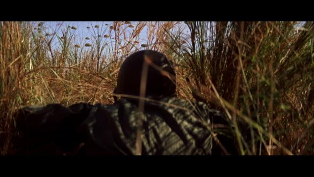 cu tu soldier crawling throough thick grass / tokyo, japan - 制服点の映像素材/bロール
