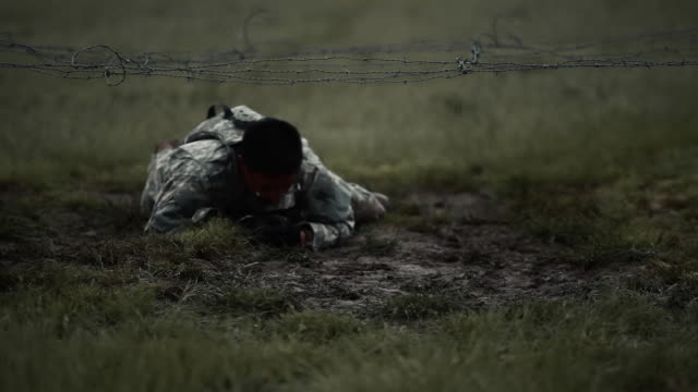 soldier crawling under low barbed wire at an obstacle course, it's muddy. - military fitness stock videos and b-roll footage