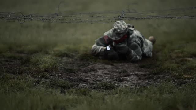 vídeos de stock, filmes e b-roll de soldier crawling under low barbed wire at an obstacle course. - campo de treinamento militar