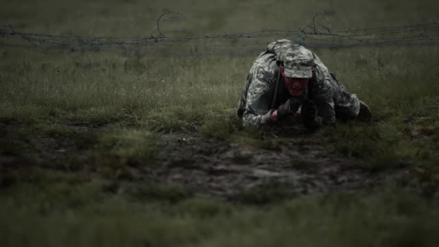 soldier crawling under low barbed wire on elbows and knees. - military uniform stock videos & royalty-free footage