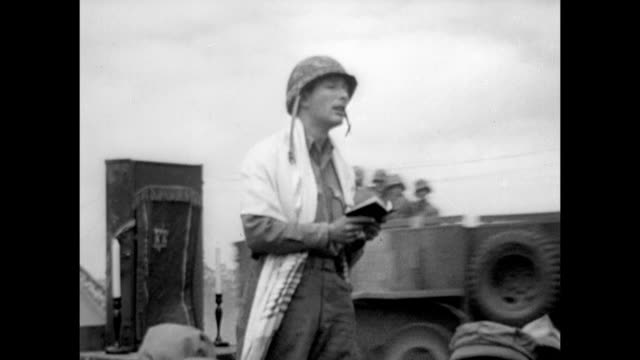soldier delivering sermon w/ bible in hand other soldiers gathered around for prayer religious service on iwo jima beach / vs us marines examining... - battle of iwo jima stock videos & royalty-free footage