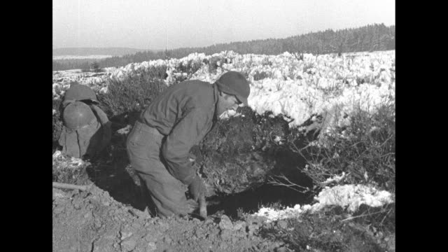 VS US soldier digs a foxhole or trench or a dugout in a snowy field on the Western Front / Note exact day not known