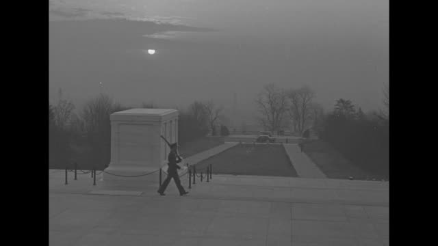 Soldier doing guard duty at Tomb of the Unknowns morning sun in background / crowd in amphitheater of cemetery gathered for service