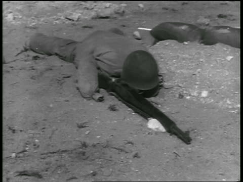 B/W 1955 soldier dummy in helmet with gun lying in dirt on ground / atomic testing in Nevada