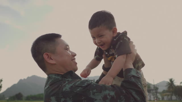 soldier father holding and playing his son in a park - military stock videos & royalty-free footage