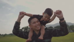 Soldier father holding and playing his son in a park
