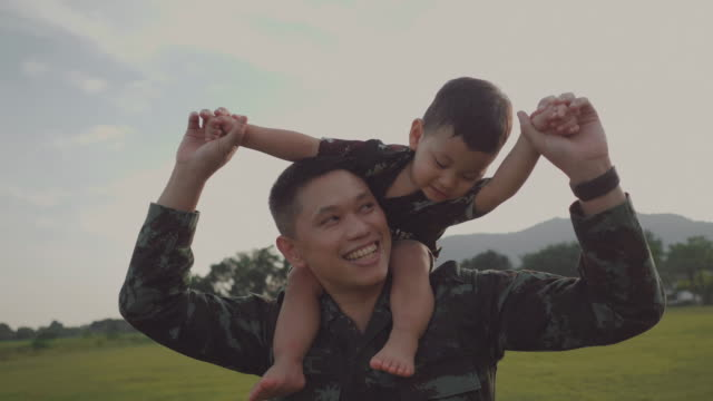 soldier father holding and playing his son in a park - war veteran stock videos & royalty-free footage