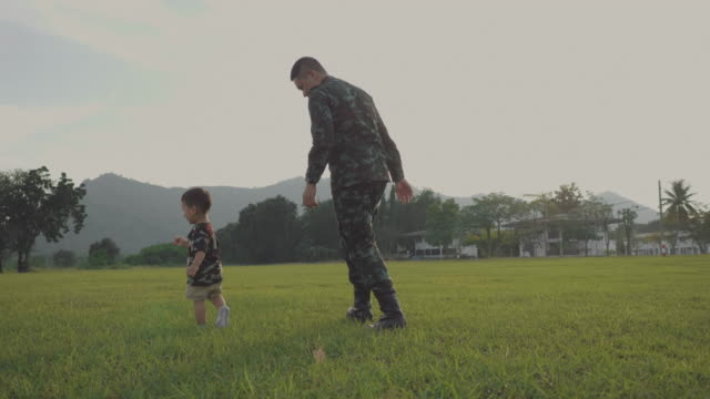 soldier father holding and playing his son in a park - son stock videos & royalty-free footage