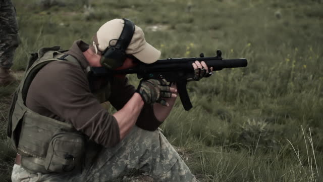 vídeos de stock e filmes b-roll de soldier finishes a round of ammunition with his mp5 - protetor de ouvido
