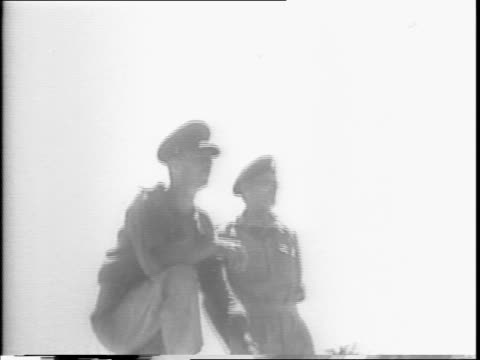 a soldier fires a machine gun / soldiers advance carefully / map of sicily show what had been taken / the british flag flies on a building / general... - 1943年点の映像素材/bロール