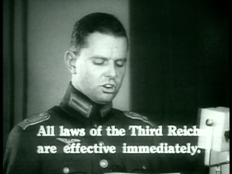 Soldier for radio 'All laws of the Third Reich effective immediately' Nazi banners hanging above peoples heads Street vendors w/ photographs of...