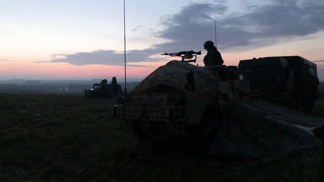 soldier from the royal anglian regiment guards the perimeter of the camp from a coyote tactical support vehicle just before sunrise during a mission... - atlantic islands stock videos & royalty-free footage