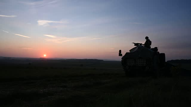 soldier from the royal anglian regiment guards the perimeter of the camp from a coyote tactical support vehicle at sunrise during a mission rehearsal... - at the edge of stock videos & royalty-free footage