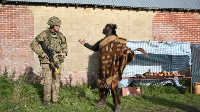 stockvideo's en b-roll-footage met soldier from the royal anglian regiment speaks with a role-play actor portraying a malian leader during a mission rehearsal exercise ahead of the uk... - british military