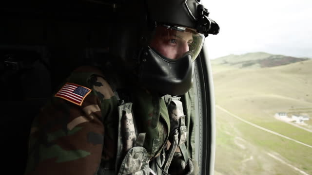 soldier gazing out of helicopter door - helicopter stock videos and b-roll footage