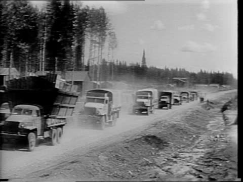 soldier gets into military truck wearing a dust mask / sign on truck reads 'alcan highway' / convoy of military trucks drive down a dirt road leaving... - alcan highway stock videos and b-roll footage