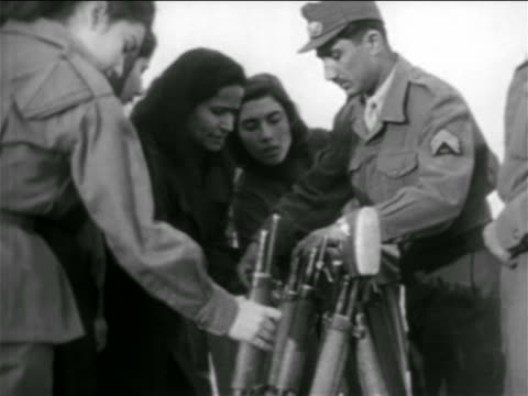 B/W 1957 soldier giving rifles out to women outdoors / Syria / newsreel