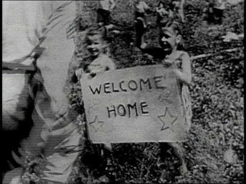 soldier greeting family on street / soldier embracing woman as crowd watches / soldier greeting children holding welcome home sign / buildings under... - world war ii stock videos & royalty-free footage