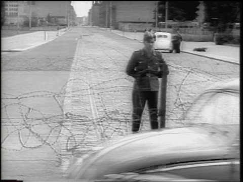 soldier guarding barbed wire fence of berlin wall / germany / newsreel - 1961 stock-videos und b-roll-filmmaterial