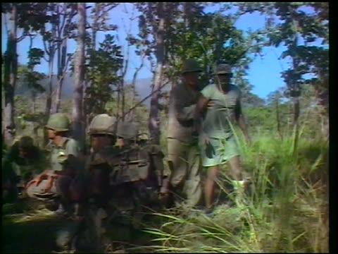 vidéos et rushes de 1965 soldier helping wounded black soldier walk past others sitting on ground in grass / vietnam - plaie
