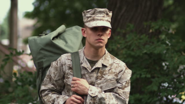 stockvideo's en b-roll-footage met sm ms portrait soldier holding knapsack and turning head to stare gravely at camera/ chicago, il - militair uniform