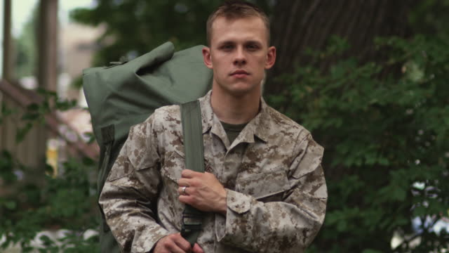 vidéos et rushes de sm ms portrait soldier holding knapsack and turning head to stare gravely at camera/ chicago, il - soldat
