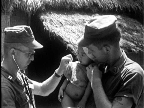 US soldier holding young Vietnamese child as American doctor with stethoscope inspects him CU face of young child / Vietnam / AUDIO