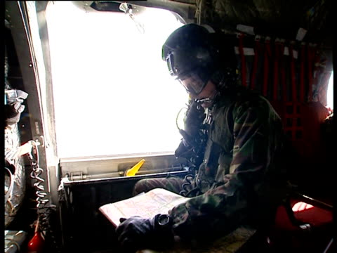 soldier holds a map while looking out of the window of a flying helicopter. - militäruniform bildbanksvideor och videomaterial från bakom kulisserna