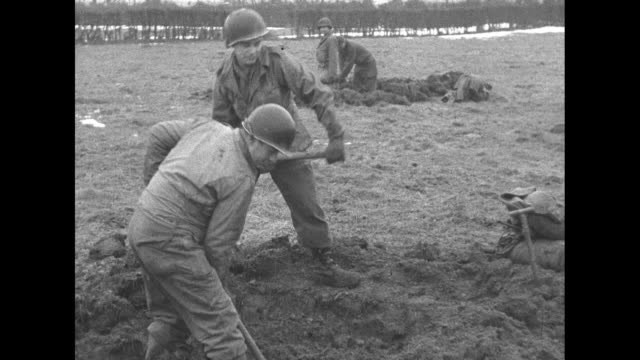 soldier holds rifle / rear shot two soldiers with heads sticking out of foxhole look at snowy field beyond / soldiers dig with shovel and pickaxe /... - trench stock videos & royalty-free footage