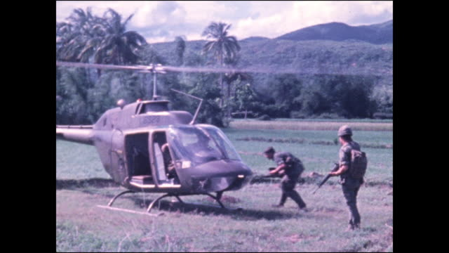 soldier holds up m-16 to guide helicopter in to land in rice paddy, man gets in and helicopter takes off. - vietnam war stock videos & royalty-free footage