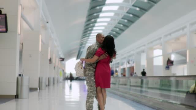 ws soldier hugs wife in airport - schuhwerk stock-videos und b-roll-filmmaterial