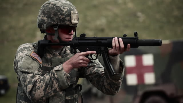 soldier in a helmet and sunglasses shooting an mp5 - mp stock-videos und b-roll-filmmaterial