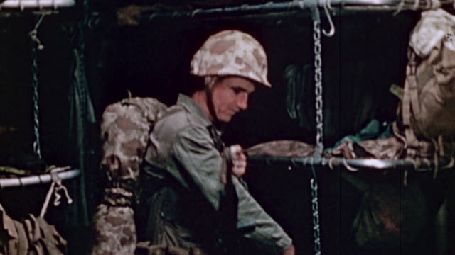Soldier in camouflage fatigues and helmet with backpack hanging rifle around shoulder in barracks and removing pinup from bulletin board