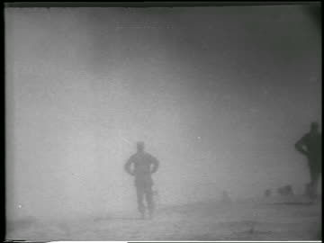 vidéos et rushes de soldier in cloud of dust / fallout from atomic bomb explosion in desert, nevada / newsreel - 1952