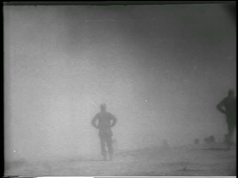 vidéos et rushes de b/w 1952 soldier in cloud of dust / fallout from atomic bomb explosion in desert nevada / newsreel - 1952