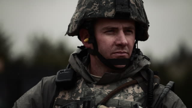 vidéos et rushes de soldier in cold weather looking around and then to camera. - soldat