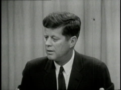 Soldier in fatigues gesturing toward open water John F Kennedy speaking at press conference JFK meeting with officials / United States