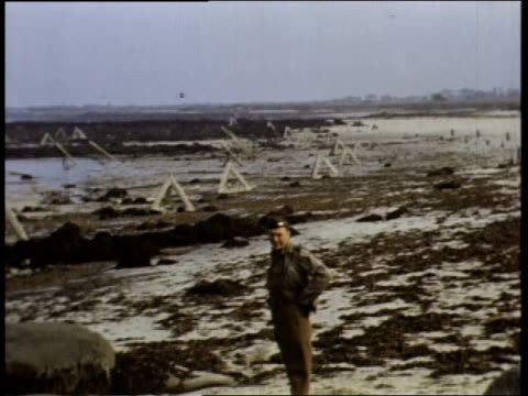 montage soldier in uniform walking on beach / normandy france - 礎石点の映像素材/bロール