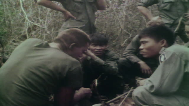 soldier interrogating captured viet cong and speaking with south vietnamese army translator / vietnam - 言語翻訳点の映像素材/bロール