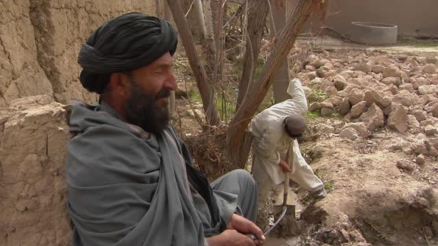 stockvideo's en b-roll-footage met soldier investigating with civilian / musa qala helmand province afghanistan - vertaling