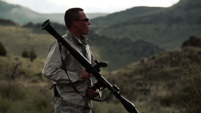 a soldier is holding a rocket propelled grenade launcher and looking around. - rocket launcher stock videos & royalty-free footage