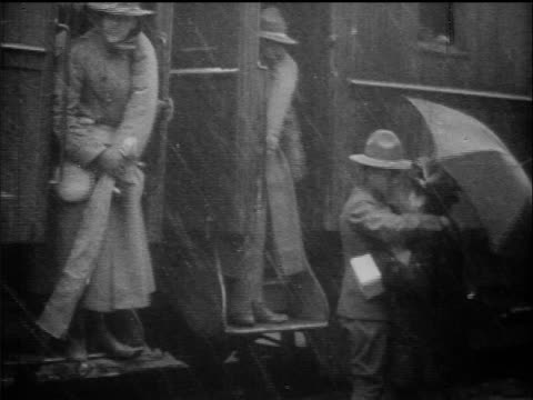 b/w 1917 soldier kissing woman with umbrella in rain before boarding train / detroit / ww i / doc - prima guerra mondiale video stock e b–roll