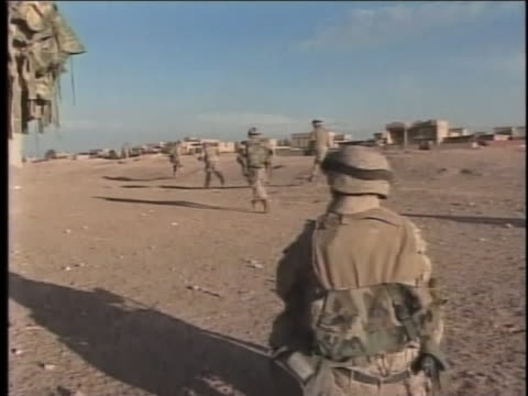 soldier kneels in the foreground as other soldiers run across the sand. - al fallujah stock videos & royalty-free footage