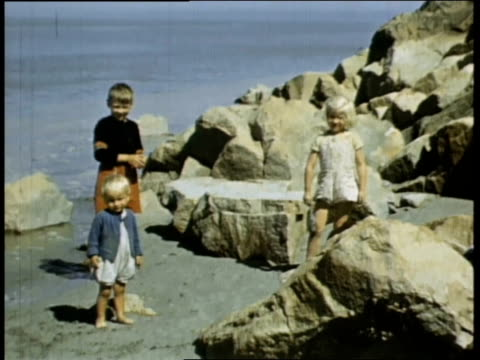 vidéos et rushes de a soldier leaning over wall to look at beach / french children playing on beach - film documentaire image animée
