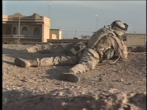 soldier lies on his stomach, looking through the scope of his weapon. - al fallujah stock videos & royalty-free footage